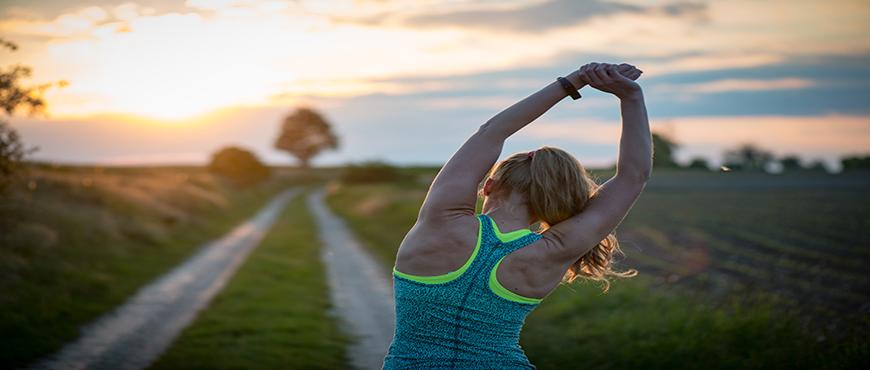 Feliz mujer deportiva exitosa levantando los brazos al cielo en la espalda